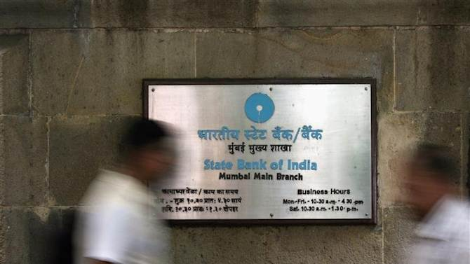People walk in front of signboard displayed at head office of State Bank of India in Mumbai