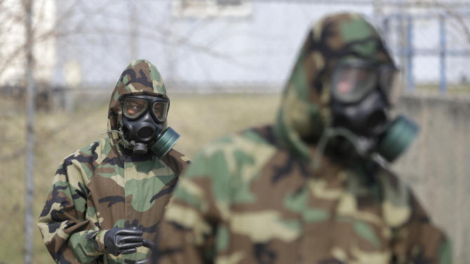 """Soldiers of the U.S. Army 23rd chemical battalion wear gas masks while attending a demonstration of their equipment during a ceremony to recognize the battalion's official return to the 2nd Infantry Division based in South Korea at Camp Stanley in Uijeongbu, north of Seoul, Thursday, April 4, 2013. The 23rd chemical battalion left South Korea in 2004 and returned with some 350 soldiers in Jan. 2013. The battalion will provide nuclear, biological and chemical detection, equipment decontamination and consequence management assistance to support U.S. and South Korean military forces. North Korea warned Thursday that its military has been cleared to attack the U.S. using """"smaller, lighter and diversified"""" nuclear weapons, while the U.S. said it will strengthen regional protection by deploying a missile defense system to Guam. (AP Photo/Lee Jin-man)"""