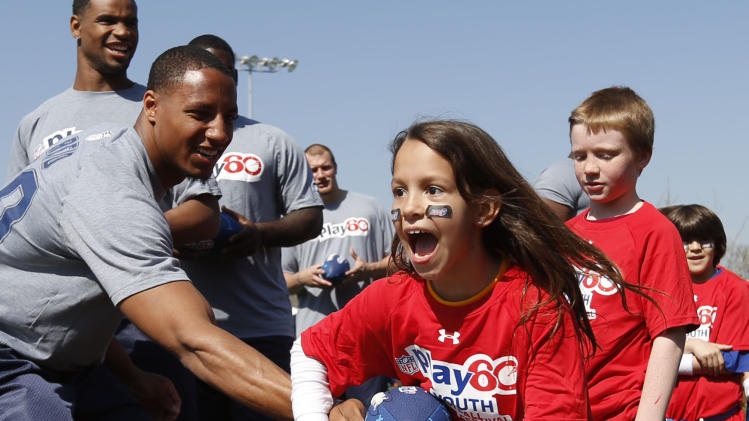 IMAGE DISTRIBUTED FOR NFL NETWORK - Draft prospect Eric Reid, of Louisiana State, hands the ball off to young football players during the NFL Play 60 Youth Football Festival, Wednesday, April 24, 2013 in New York. (Jason DeCrow/AP Images for NFL Network)