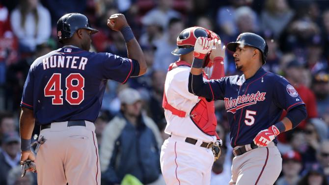 Minnesota Twins left fielder Eduardo Escobar, right, is congratulated by teammate Torri Hunter after his two-run, home run against the Boston Red Sox during the ninth inning in the first baseball game of a doubleheader at Fenway Park in Boston, Wednesday, June 3, 2015. (AP Photo/Charles Krupa)