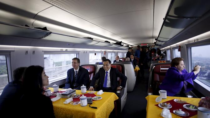 China's Premier Li sits with Serbia's PM Vucic and Latvia's PM Straujuma on a CRH Harmony bullet train to Shanghai from Suzhou Railway Station, near Shanghai