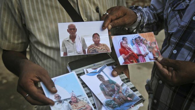 Indian people show photos of their loved ones who went missing during monsoon flooding near the gate of an airport in Jollygrant, in the northern Indian state of Uttarakhand, India, Wednesday, June 26, 2013. Paramilitary soldiers on Wednesday recovered 20 bodies from a steep hillside in northern India where a helicopter crashed while on a mission to rescue people stranded in monsoon floods, the country's air force chief said. (AP Photo/Rafiq Maqbool)