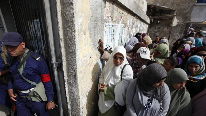 A Navy officer stands guard as Egyptian women line up outside a polling station to cast their votes during the first day of the presidential elections in Alexandria, Egypt, Wednesday, May 23, 2012. Egyptians went to polls on Wednesday morning to elect a new president after the fall of ex-President Hosni Mubarak last year. (AP Photo/Khalil Hamra)