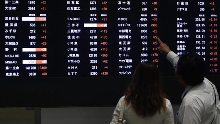 A visitor points at a stock price displayed on an electronic board at the Tokyo Stock Exchange in Tokyo September 9, 2013. REUTERS/Yuya Shino/Files