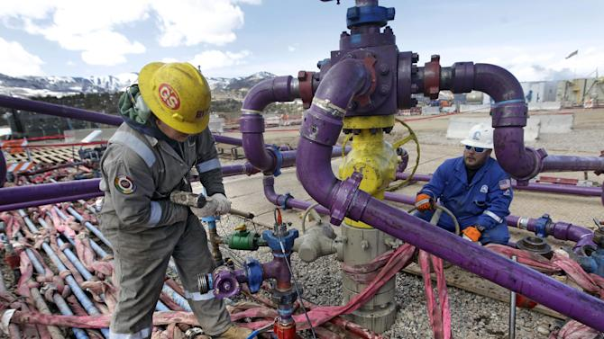 In this March 29, 2013 photo, workers tend to a well head during a hydraulic fracturing operation at an Encana Oil & Gas (USA) Inc. gas well outside Rifle, in western Colorado. The first experimental hydraulic fracturing occurred in 1947. More than 1 million U.S. oil and gas wells have been fracked since, according to the American Petroleum Institute. (AP Photo/Brennan Linsley)