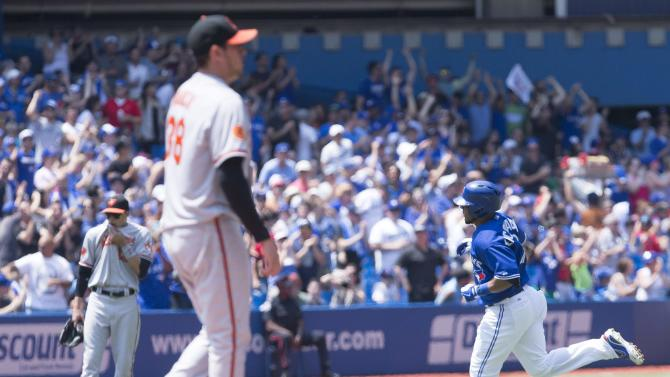 Toronto Blue Jays' Edwin Encarnacion, right, rounds the bases after hitting a two-run home run off Baltimore Orioles starting pitcher Freddy Garcia, foreground, during second-inning baseball game action in Toronto, Sunday June 23, 2013. (AP Photo/The Canadian Press, Chris Young)