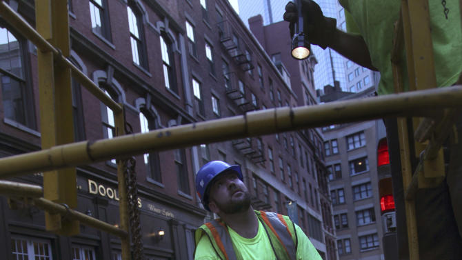 Fiberoptic technician Daniel Haire of Phoenix Communications kneels on a street as he talks with co-workers illuminating a man hole with a flash light in the Financial District of Boston, at dusk Thursday, July 21, 2011.  The killer lurking in the shadows of the current heat wave may be the hot nights. (AP Photo/Charles Krupa)