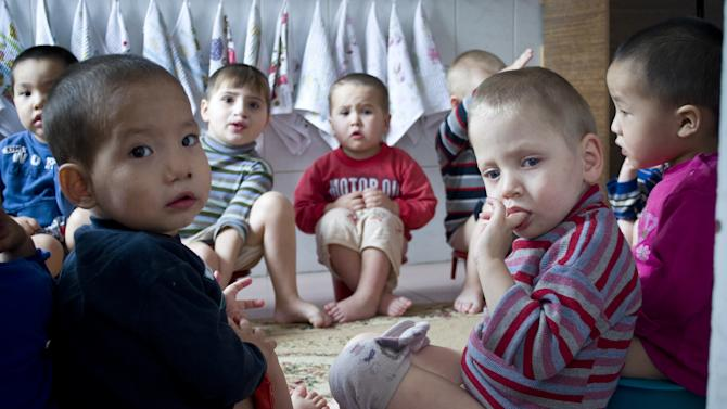 Kyrgyz orphans look on in an orphanage in Bishkek, Kyrgyzstan, Thursday, Jan. 31, 2013. Americans were in process of adopting 65 orphans from Kyrgyzstan when it suspended international adoptions in 2008 due to allegations of fraud. Some of the Americans gave up, some of the children were placed in domestic adoptions, and last summer nine of the remaining children finally were allowed to go to America. There are now 16 U.S. families still waiting, five year later. (AP Photo/Abylay Saralayev)