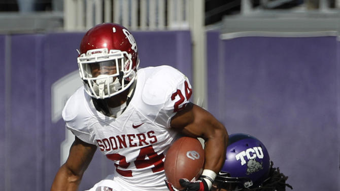 Oklahoma running back Brennan Clay (24) finds running room as TCU's Jason Verrett (2) attempts the tackle in the first half of an NCAA college football game Saturday, Dec. 1, 2012, in Fort Worth, Texas. (AP Photo/Tony Gutierrez)
