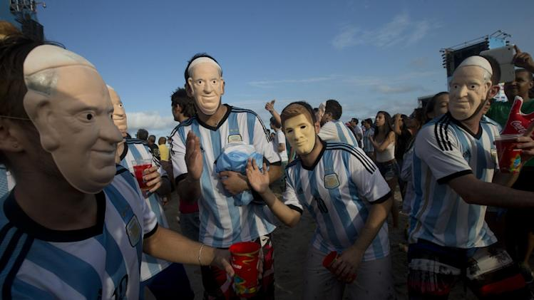 "FILE - In this Wednesday, July 9, 2014 file photo, soccer fans of the Argentina national soccer team wear masks with faces of Pope Francis and Argentine soccer player Lionel Messi during a live telecast of the soccer World Cup semifinal match between Argentina and Netherlands, inside the FIFA Fan Fest area on Copacabana beach, in Rio de Janeiro, Brazil. The Vatican says it is unlikely that Pope Francis and his predecessor, Pope Emeritus Benedict XVI, would get together to watch their home teams in the World Cup final on Sunday. Vatican spokesman, the Rev. Federico Lombardi, said Thursday, July 10, 2014 that the hour of the final is late for Francis' routine, and acknowledged with a chuckle that Benedict wasn't known as an avid sports fan. Still, he didn't rule anything out, saying, ""we'll see in the coming days."" Pope Francis has already given his word that there would be no papal intervention in Argentina's fortunes, promising he wouldn't pray for any team. German-born Benedict's interests are known to lean more toward intellectual than athletic pursuits. (AP Photo/Silvia Izquierdo, File)"