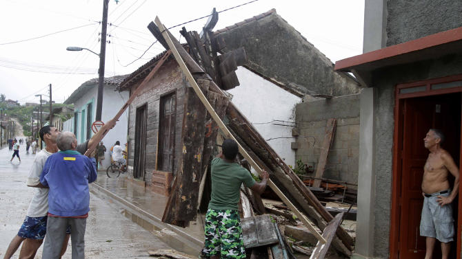 Men try to free an electrical wire wire from debris, which was turned off last night, after the passing of Hurricane Sandy in Gibara, Cuba, Thursday, Oct. 25, 2012. Hurricane Sandy blasted across eastern Cuba on Thursday as a potent Category 2 storm and headed for the Bahamas after causing at least two deaths in the Caribbean. (AP Photo/Franklin Reyes)
