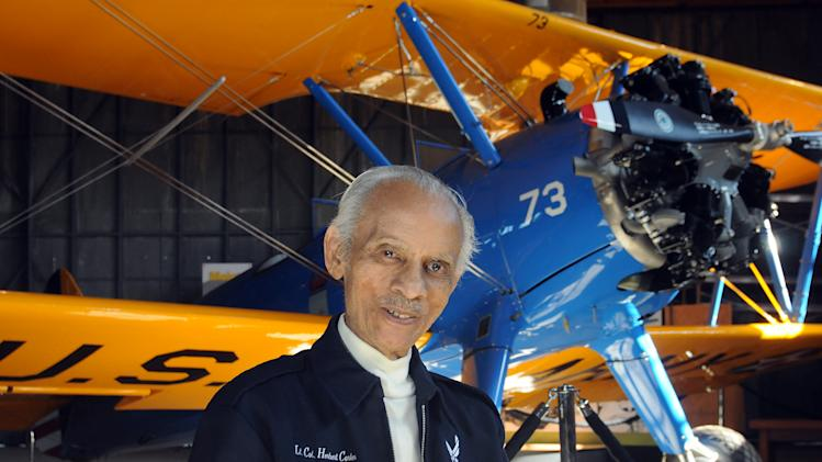 "Former Tuskegee Airman Herbert Carter, 94, of Tuskegee, Ala., poses with a PT-17 trainer aircraft in a hangar at Tuskegee Airmen National Historic Site at Moton Field in Tuskegee, Ala., Wednesday, Jan. 18, 2012.  ""Red Tails,"" a film that chronicles the heroism of the Tuskegee Airmen, opens Friday, Jan. 20. (AP Photo, David Bundy)"