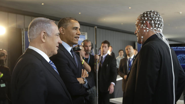 U.S. President Barack Obama, second left, and Israeli Prime Minister Benjamin Netanyahu, left, talk with Professor Amir Geva, right, wearing a device to monitor brain activity, during their tour of the Technology Expo in Jerusalem, Israel,Thursday, March 21, 2013. (AP Photo/Pablo Martinez Monsivais)