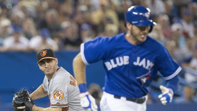 Baltimore Orioles pitcher Miguel Gonzalez, left, lines up a throw to first base to out Toronto Blue Jays' J.P. Arencibia during the fourth inning of a baseball game in Toronto, Saturday, June 22, 2013. (AP Photo/The Canadian Press, Chris Young)