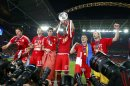 Bayern Munich's Boateng lifts the trophy while celebrating with team mates in front of photographers after defeating Borussia Dortmund in their Champions League Final soccer match at Wembley Stadium in London