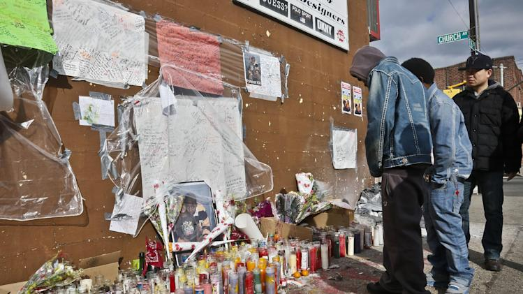 "People visit a growing makeshift memorial for police shooting victim Kimani ""Kiki"" Gray on Thursday, March 14, 2013 in the East Flatbush neighborhood of Brooklyn, N.Y.  The 16-year-old was shot to death on a Brooklyn street last Saturday night by plainclothes police officers. (AP Photo/Bebeto Matthews)"