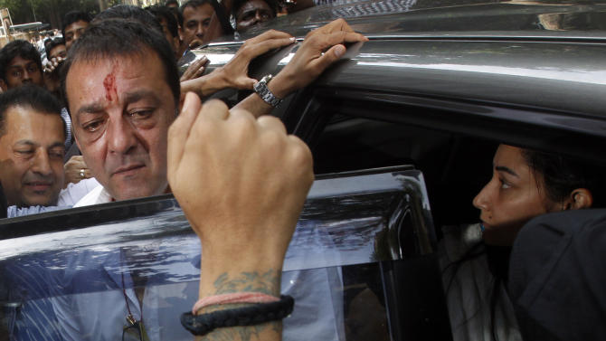 Bollywood star Sanjay Dutt, second left, arrives with wife Manyata, right, to surrender before a court in Mumbai, India, Thursday, May 16, 2013. Dutt has been sentenced to five years in prison for a 1993 weapons conviction linked to a deadly terror attack in Mumbai that killed 257 people. The 53-year-old actor served 18 months in jail before being released on bail in 2007 pending an appeal. The Supreme Court reduced his prison sentence to five years from the six-year term initially handed down. (AP Photo/Rajanish Kakade)