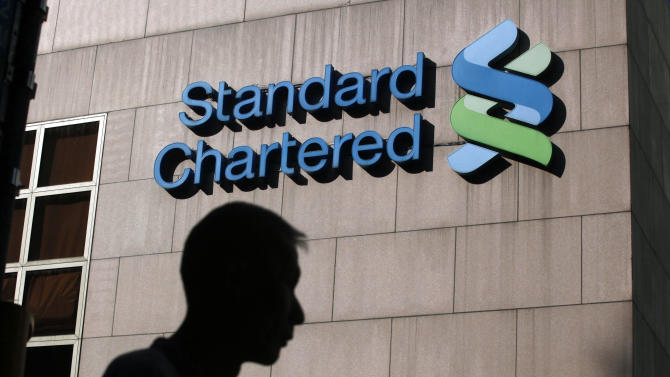 """FILE - In this Oct. 13, 2010 file photo, a man walks past the Standard Chartered Bank building in Hong Kong. The London-based bank schemed with the Iranian government to launder $250 billion from 2001 to 2007, leaving the United States' financial system """"vulnerable to terrorists,"""" New York's financial regulator charged Monday, Aug. 6, 2012. (AP Photo/Kin Cheung, File)"""
