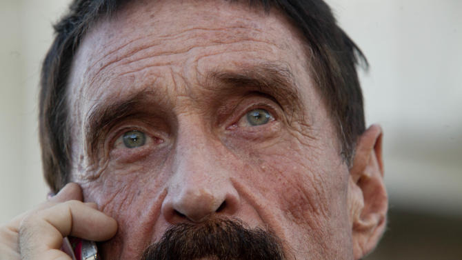 """Software company founder John McAfee talks on his mobile phone after a press conference outside the Supreme Court in Guatemala City, Tuesday, Dec. 4, 2012. McAfee, 67, who has been identified as a """"person of interest"""" in the killing of his neighbor in Belize, 52-year-old Gregory Faull, has surfaced in public for the first time in weeks, saying Tuesday that he plans to ask for asylum in Guatemala because he fears persecution in Belize. (AP Photo/Moises Castillo)"""
