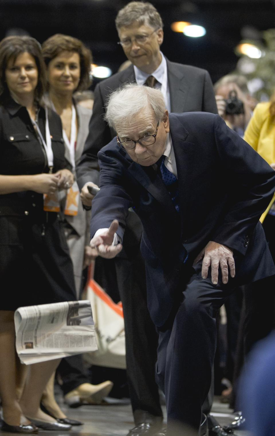 Warren Buffett, chairman and CEO of Berkshire Hathaway tosses a newspaper during a newspaper tossing competition in Omaha, Neb., Saturday, May 5, 2012. Bill Gates watches at rear. Berkshire Hathaway is holding it's annual shareholders meeting this weekend. (AP Photo/Nati Harnik)