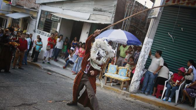 "A dancer waving a whip during the ""Paseo del Pendon"", a traditional artistic march in Chilpancingo"