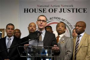 Barneys New York Chief Executive Mark Lee speaks to the media next to Reverend Al Sharpton during a news conference in New York
