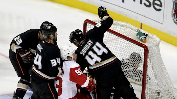 Detroit Red Wings left wing Johan Franzen, center, scores between Anaheim Ducks center Daniel Winnik, left, and Sheldon Souray during the second period in Game 2 of their first-round NHL hockey Stanley Cup playoff series in Anaheim, Calif., Thursday, May 2, 2013. (AP Photo/Chris Carlson)
