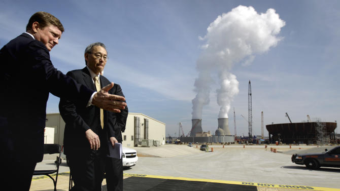 FILE- In this Feb. 15, 2012 file photo, U.S. Secretary of Energy Secretary Steven Chu, right, exits the stage with Southern Company President and CEO Thomas Fanning as cooling towers for units 1 and 2 are seen in the background at left as the new reactor vessel bottom head for unit 3stands under construction at right, on a visit of the Vogtle nuclear power plant in Waynesboro, Ga. Vogtle  initially estimated to cost $14 billion, has run into over $800 million in extra charges related to licensing delays. A state monitor has said bluntly that co-owner, Southern Co. can't stick to its budget. The plant, whose first reactor was supposed to be operational by April 2016, is now delayed seven months. (AP Photo/David Goldman, File)