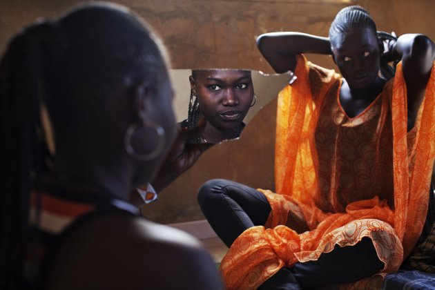 Bineta Ndiaye looks at herself in the mirror as her friend Coumba Faye fixes her hair in Faye's house in the village of Ndande