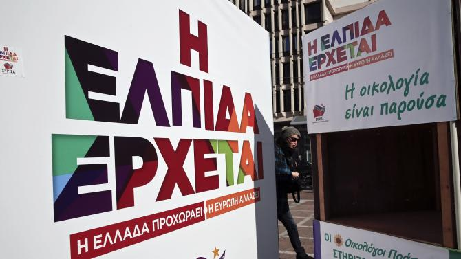 A woman is seen between disassembled parts of the Syriza party's election kiosk in Athens