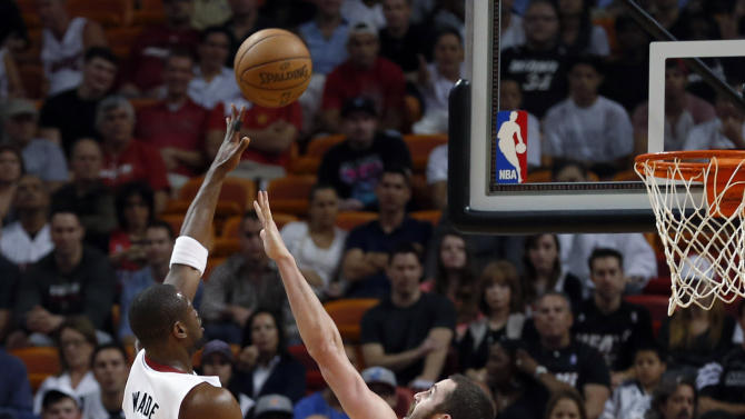 Miami Heat's Dwyane Wade (3) shoots over Minnesota Timberwolves' Kevin Love (42) during the first half of an NBA basketball game Tuesday, Dec 18, 2012, in Miami. (AP Photo/Alan Diaz)