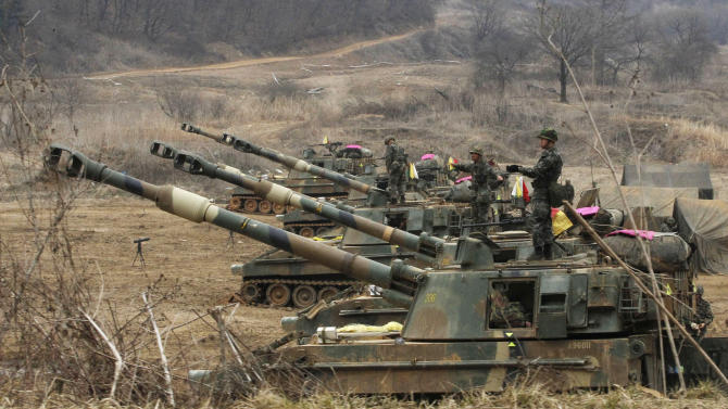 South Korean marines stand on their K-55 self-propelled howitzers during an exercise against possible attacks by North Korea near the border village of Panmunjom in Paju, South Korea  Monday, April 1, 2013.  After weeks of war-like rhetoric, North Korean leader Kim Jong Un gathered legislators Monday for an annual spring parliamentary session taking place one day after top party officials adopted a statement declaring building nuclear weapons and the economy the nation's top priorities.(AP Photo/Ahn Young-joon)