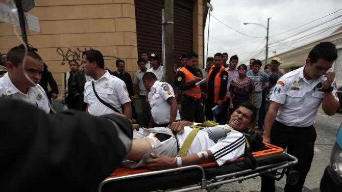 Rescuers evacuate a man injured during a shooting in a downtown street of Guatemala City