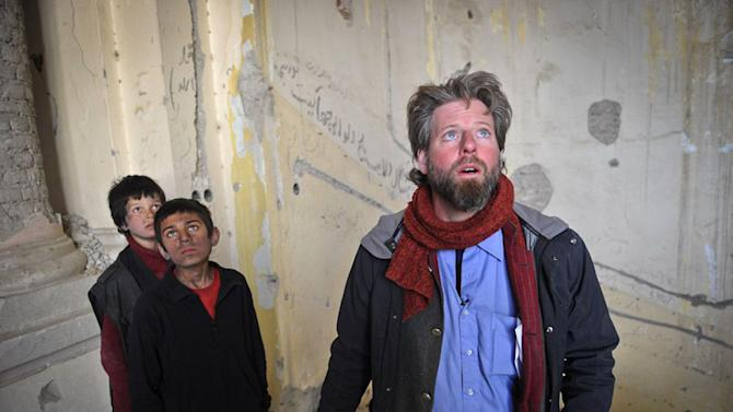 "An undated production still photograph from the Oscar-nominated film, ""Buzkashi Boys,"" which was filmed in Kabul, Afghanistan, shows actors Jawanmard Paiz, left, Fawad Mohammadi, center, and director Sam French at work on the set of the film. The actors were plucked from the dingy streets of the Afghan capital to be the main stars of ""Buzkashi Boys,"" a coming-of-age movie filmed entirely in a war zone and nominated in the Best Live Action Short Film category. The movie is about two penniless young boys _ a street urchin and a blacksmith's son _ who are best friends and dream of becoming professional players of buzkashi, a brutal, polo-like game in which horseback riders wrangle to get a headless goat carcass into a circular goal at one end of the field. (AP Photo/David Gill, Afghan Film Project)"
