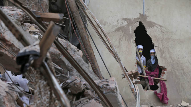 Bangladeshi rescue workers watch from a damaged section of a wall at the site of a building that collapsed Wednesday in Savar, near Dhaka, Bangladesh, Thursday, April 25, 2013. By Thursday, the death toll reached at least 194 people as rescuers continued to search for injured and missing, after a huge section of an eight-story building that housed several garment factories splintered into a pile of concrete. (AP Photo/Kevin Frayer)