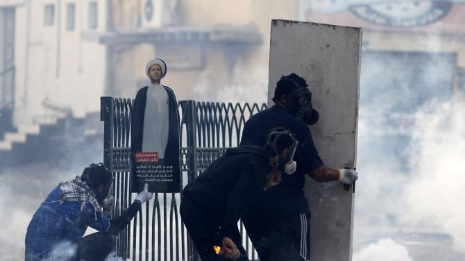 A protester holding a molotov looks out as his fellow protester provides shelter with a wooden board during clashes in the village of Bilad Al Qadeem south of Manama