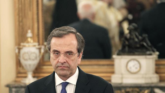 FILE - Greek conservative leader Antonis Samaras takes part in a swearing in ceremony officiated by Greece's Orthodox Archbishop Ieronimos at the Presidential palace in Athens, in this Thursday, June 21, 2012 file photo. Samaras underwent surgery for a detached retina Saturday June 23, 2012. Government spokesman Simos Kedikoglou said Sunday that the doctor treating him had forbidden him from flying. So he will not be well enough to travel to a critical European Union summit in Brussels .  (AP Photo/Petros Giannakouris, File)