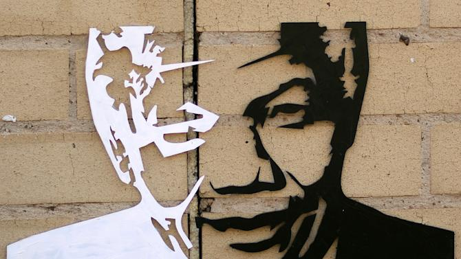 FILE - In this July 16, 2013 file photo, a portrait of former South African President Nelson Mandela is attached to a wall outside the Mediclinic Heart Hospital where he was being treated in Pretoria, South Africa. On Thursday, Dec. 5, 2013, Mandela died at the age of 95. (AP Photo/Themba Hadebe)