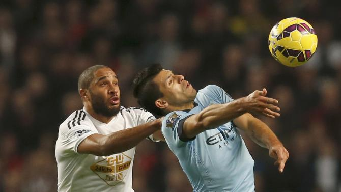 Manchester City's Sergio Aguero is challenged by Swansea City's Ashley Williams during their English Premier League soccer match at the Etihad stadium in Manchester