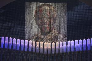 Candles are lit under a portrait of Neslon Mandela…