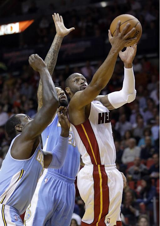 Miami Heat guard Dwyane Wade (3) prepares to shoot against Denver Nuggets forward Wilson Chandler (21) and J.J. Hickson, left, during the first  half of an NBA basketball game in Miami, Friday, March