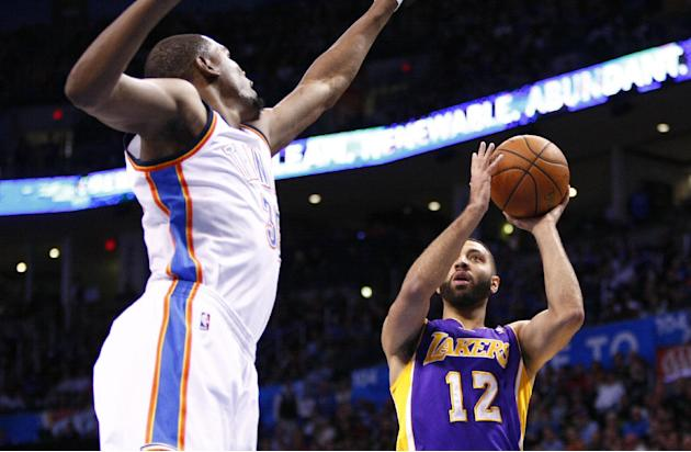 Los Angeles Lakers guard Kendall Marshall (12) shoots in front of Oklahoma City Thunder forward Kevin Durant (35) during the first quarter of an NBA basketball game in Oklahoma City, Thursday, March 1