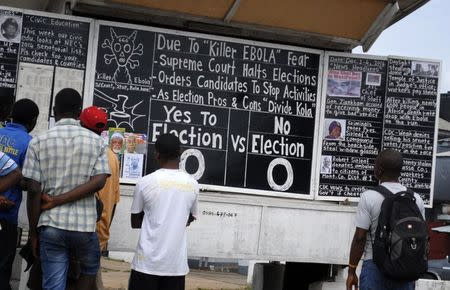 Bystanders read the headlines illustrating the battle over the holding of elections in Liberia amid the Ebola crisis at a street side chalkboard newspaper in Monrovia