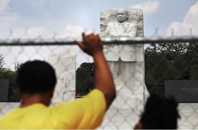 Visitors to the Rev. Martin Luther King Jr. Memorial stand behind security fencing on the National Mall in Washington Sunday, Aug., 21, 2011. The memorial to the late civil rights leader is scheduled