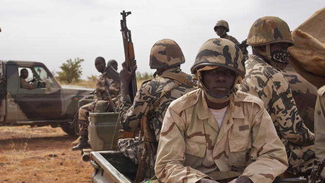 """In this Nov. 24, 2012 photo, soldiers from a Malian army special unit sit atop pick-ups, following a training exercise in the Barbe military zone, in Mopti, Mali.  Secretary-General Ban Ki-moon said Friday, Jan. 11, 2013 that France, Senegal and Nigeria have responded to an appeal from Mali's President Dioncounda Traore for help to counter an offensive by al-Qaida-linked militants who control the northern half of the country and are heading south. The U.N. chief said that assisting the Malian defense forces push back against the Islamist armed groups is """"very important.""""(AP Photo/Francois Rihouay)"""