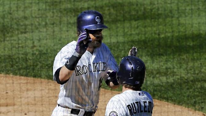 Colorado Rockies' Charlie Blackmon, left, is congratulated by Josh Rutledge (14) after hitting a solo home run against the Los Angeles Dodgers during the third inning of a baseball game Wednesday, Sept. 17, 2014, in Denver. (AP Photo/Jack Dempsey)