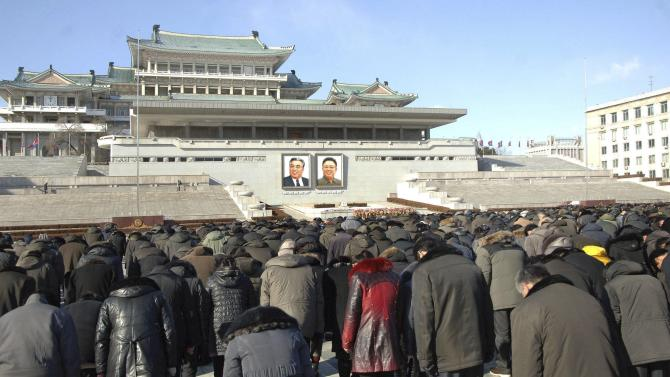 North Koreans bow as they pay respects to mark the third anniversary of the death of former leader Kim Jong Il in Pyongyang