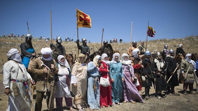 Enthusiasts wearing costumes stand together during a re-enactment of a Crusaders battle in Israel's Galilee region