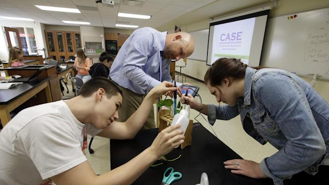 Chase Martin, left, and Harley Brown work with teacher Chris Kaufman on a project during Plant and Soil Science class at Beech Grove High School Wednesday, April 30, 2014, in Indianapolis. High school agriculture programs sprouting across the nation's Corn Belt are teaching teenagers, many of them in urban environments, that careers in the field often have nothing to do with cows and plows. (AP Photo/Darron Cummings)
