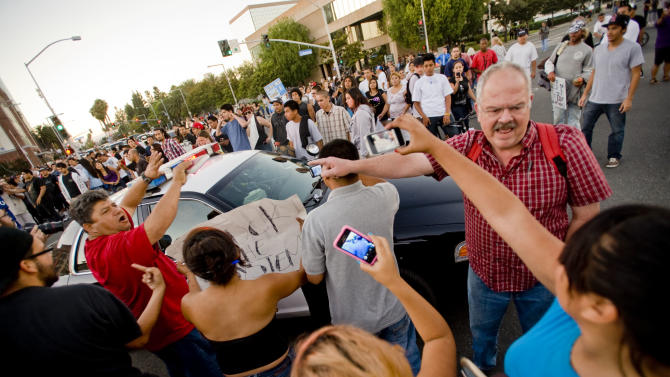 A large crowd of protesters gathered at the intersection of Broadway and Anaheim Blvd. attempt to block police cars from passing. Back-to-back weekend shootings by police have sparked four days of protests. (AP Photo/The Orange County Register,Paul Rodriguez )   MAGS OUT; LOS ANGELES TIMES OUT